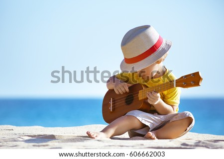 Little boy plays on Hawaiian guitar or ukulele at sea beach background. Space for text #606662003