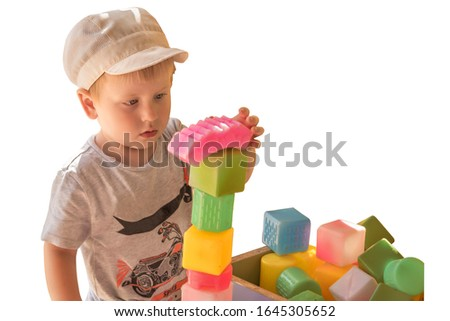 Little boy plays with colored cubes, builds a pyramid. Photo isolated