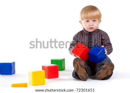 little boy plays with colorful cubes isolated on white