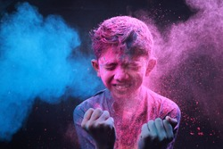 Little boy plays with colors.Concept for Indian festival Holi.