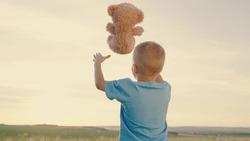 Little boy plays with his favorite soft toy bear on playground. Child throws Teddy bear up. Plush toy in hands of kid in summer park. Happy kid plays with toy, dreams in outdoors. Best friends