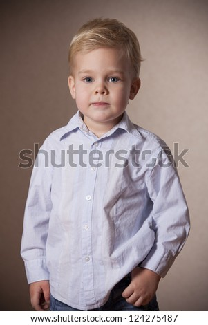 little boy portrait in shirt and jeans in studio