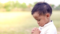 Little boy praying on nature background. Little boy praying to god. Christianity concept. Pray background. Faith hope love concept.