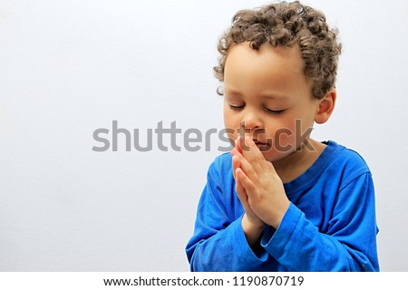 little boy praying to God stock image with hands held together with closed eyes  stock photo #1190870719