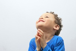 little boy praying to God stock image with hands held together with open eyes with people stock photography stock photo