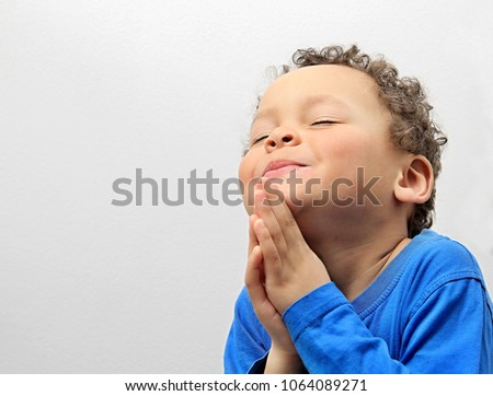 little boy praying to God with hands held together and smiling stock photo