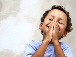 little boy praying to God with hands together and a smile on his face with  head held high stock image stock photo photo