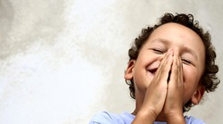 little boy praying to God with hands together and a smile on his face with head held high stock photo