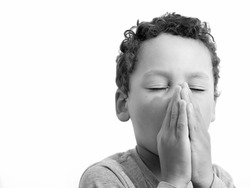 little boy praying to God with hands together stock photo