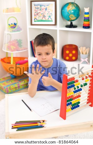 Little boy preparing for elementary school doing simple math exercises