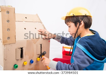 58e6613d418 Little boy pretend as a mechanic use tools fix the paper house  373984501