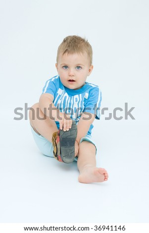 little boy putting his shoes on by himself