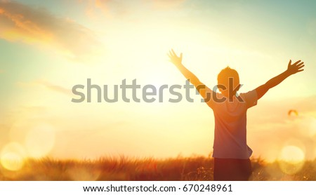 Little boy raising hands over sunset sky, enjoying life and nature. Happy Kid on summer field looking on sun. Silhouette of male child in sunlight rays. Fresh air, environment concept. Dream of flying #670248961