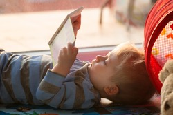 Little boy reading a book on the floor