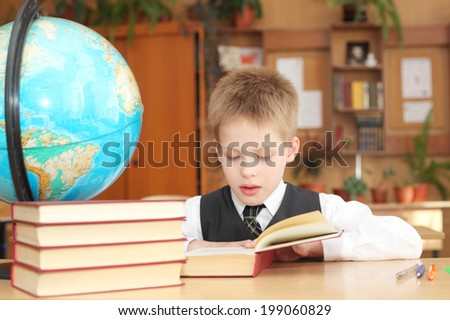 little boy reading book in the classroom