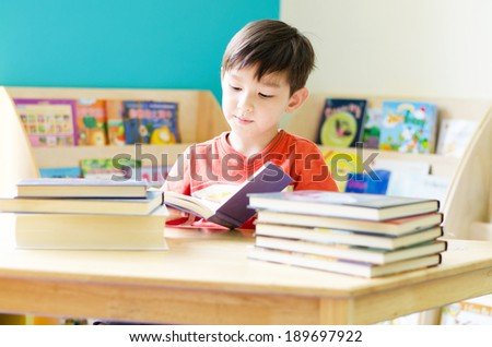 Little boy reading book on table at home