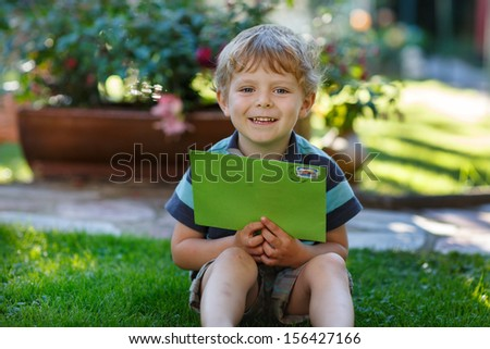 Little boy reading his first letter from a friend