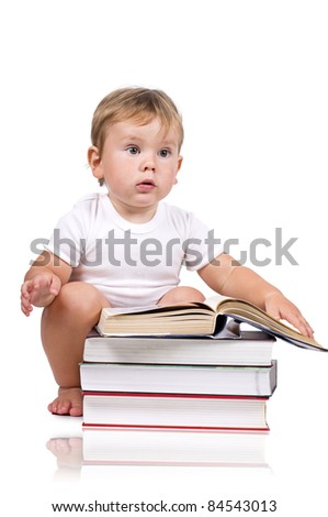 Little boy reading next to a pile of books. Isolated on white.
