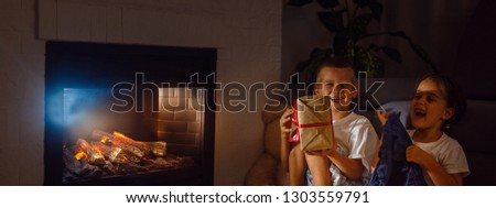 Little boy receiving a giftbox with red ribbon. Girl sitting beside