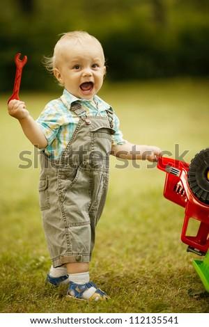 little boy repairs toy car