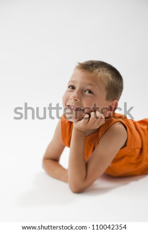 Little boy resting on the floor and smiling at camera