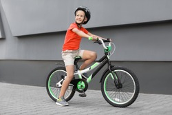 Little boy riding bicycle on street near gray wall