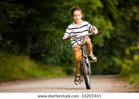 Little Boy riding his bicycle on a dirt road in the woods