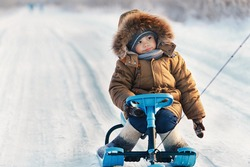 Little boy riding his kids snowmobile winter snow-covered road in the cold