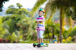 Little boy riding scooter. Kids ride kick board. Child playing on suburban street on sunny summer day. Safe helmet for children. Healthy outdoor activity. Cute kid on his way to school.