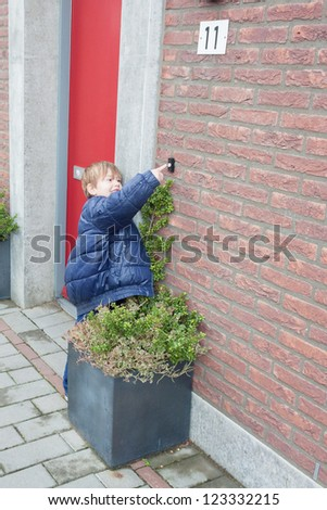 Little boy ringing door bell