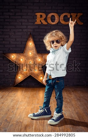 Little Boy Rock Star Giving The Rock And Roll Sign On Brick Wall Background