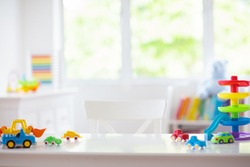 Little boy room. Desk with colorful toy cars. Nursery for young kid with educational vehicle and transport toys. Plastic car at rainbow parking garage. Home or kindergarten interior.