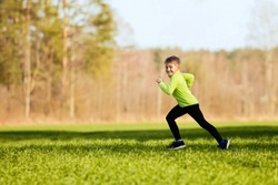 LITTLE BOY RUNNING AND EXERCISING IN GRASS FIELD NEAR THE FOREST PARK