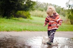 Little boy running around the puddles