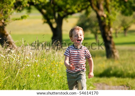 Little boy running down a dirtpath in a beautiful landscape in summer, very light and happy scene