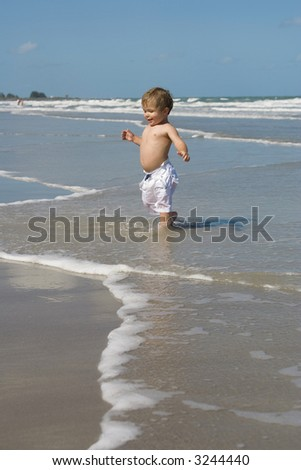 Little boy running out of water on a beach.