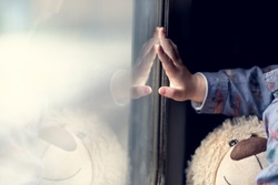 Little boy's hand touches the window on the train. Little boy travels with a toy mascot. Artistic shots with shallow depth of field.