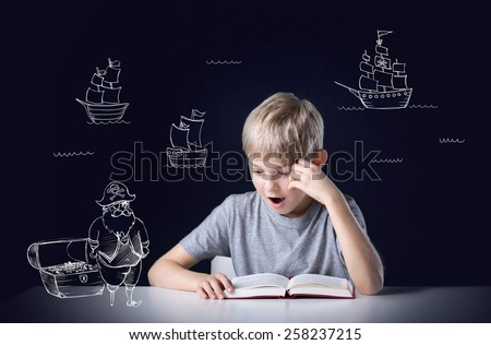 Photo of Little boy's imagination during reading the adventure book