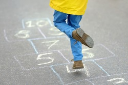 Little boy's legs and hopscotch drawn on asphalt. Child playing hopscotch game on playground on spring day. Outdoors activities for children.