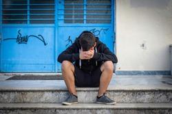 Little boy sad sitting alone at school hides his face