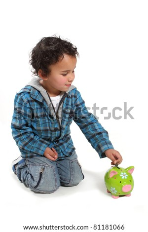 Little boy saving his money by putting it into a piggy bank