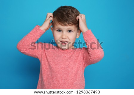 Little boy scratching head on color background. Annoying itch #1298067490