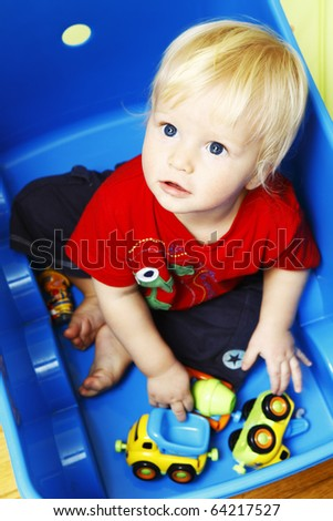 Little boy seating in blue box and playing with toys