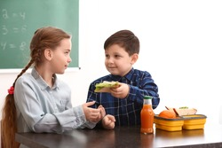 Little boy sharing his school lunch with girl in classroom