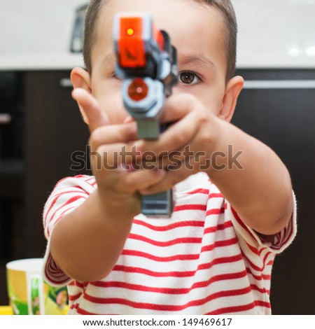 Little boy shooting a toy gun - stock photo