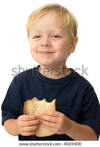 Little boy showing satisfaction while eating a peanut butter sandwich - stock photo
