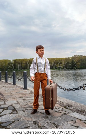 little boy simpleton in an old-fashioned rustic clothes with a vintage suitcase standing at the arrival station on the pier of the lake river - Shutterstock ID 1093991036