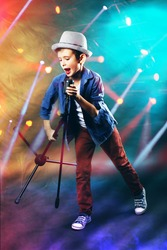 Little boy singing with microphone on laser rays background