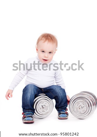 Little boy sit on iron weight, looking at camera