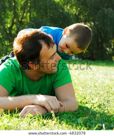 Little boy sit on the father's back and playing